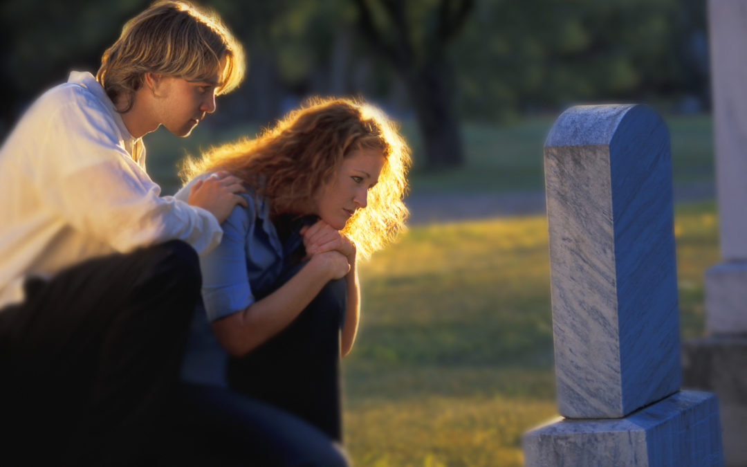 Grieving people at a gravesite